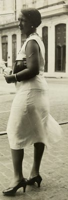 standing woman wearing a sleeveless dress, stockings and heels, carrying a clutch bag and a small package