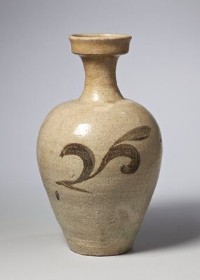 vase with pale gray-blue glaze and dark stylized leaf pattern on two sides; narrow foot with widening at shoulder; narrow neck; cupped mouth with high vertical lip