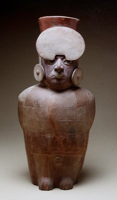 Vase in the from of a chieftain with ear plugs and large headdress. Arms bound in back indicate the status of a prisoner.