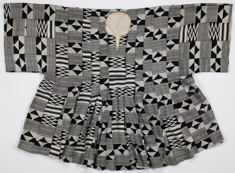 pull-over shirt made from black and white stripwoven cloth, with geometric designs of stripes, stepped shapes and zigzags; upper body lined, with lining trim at bottom hem and sleeve cuffs, of white fabric with pastel colors of occasional print