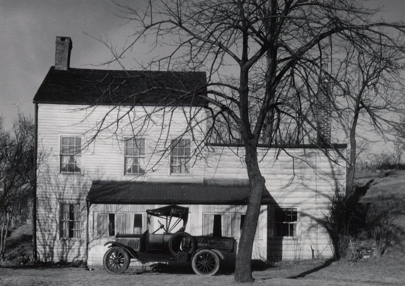 old pickup truck parked beside a white two-story house with two lean-to additions; bare tree behind truck