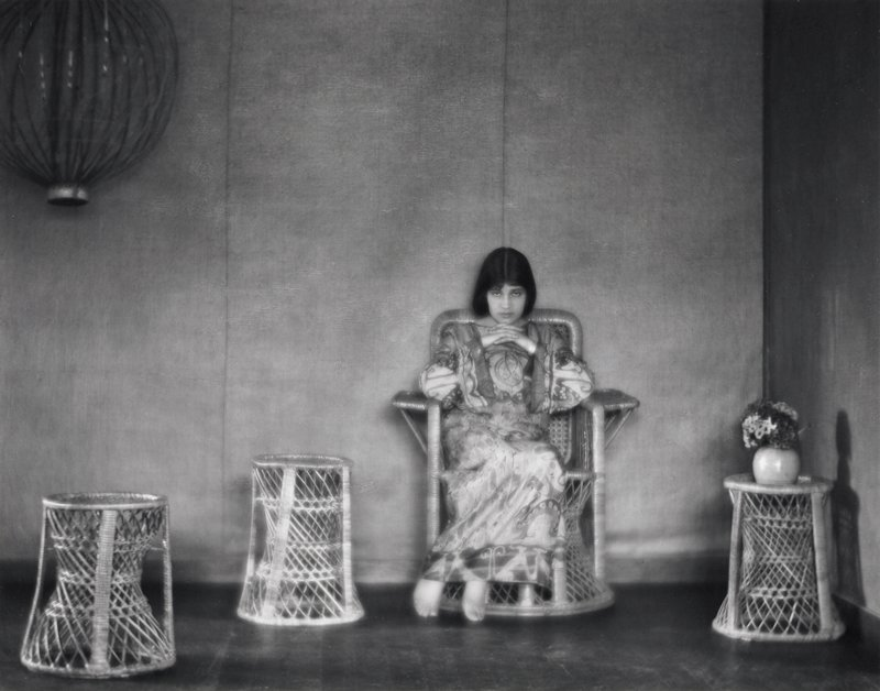 woman with shoulder-length dark hair wearing a long Art Deco print shift, seated in a wicker chair; three wicker stands--one at right holds round vessel of flowers; round lantern (?), ULC