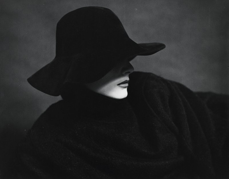 head and shoulders of woman dressed in black with black hat; chin highlighted