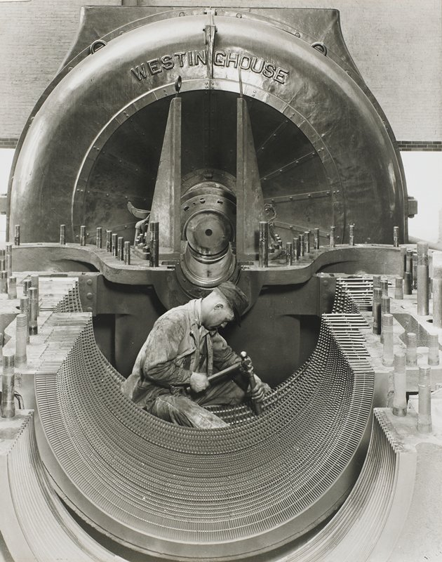"man wearing a cap and work clothes hammering on the lower half of a large machine; machine says ""WESTINGHOUSE"" at top"