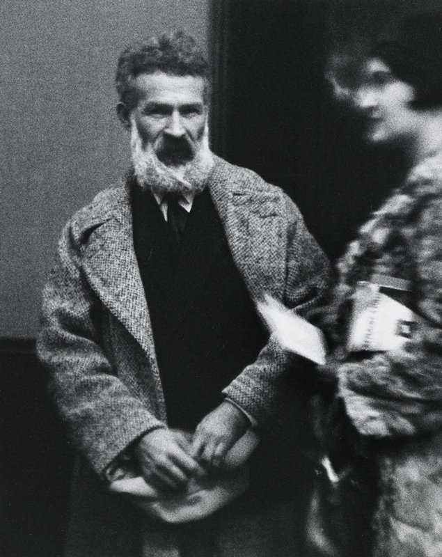 blurry portrait of a standing man wearing a jacket, tie, and a tweed overcoat, with bushy white beard; woman, facing left, at right edge
