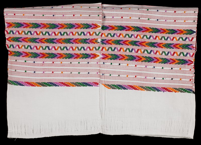 white with groups of three red narrow stripes hidden in the weft; decorated with multicolored dots, flowers, zigzags, chevrons and lines, V-neck