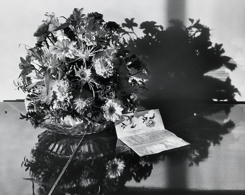 bouquet of flowers on a cut glass plate; letter at right with birds and nest on top of sheet