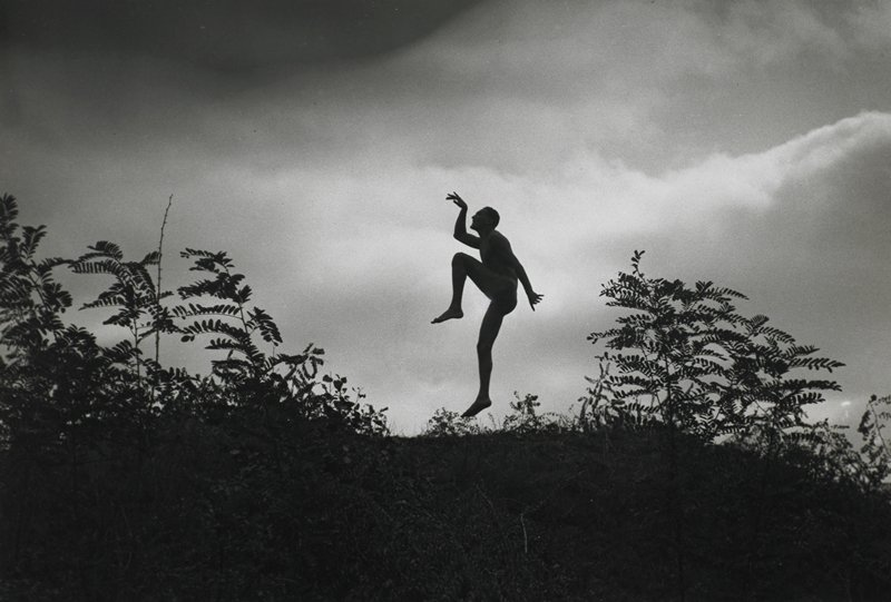 nude man in profile, jumping; foliage on either side of man; cloudy sky