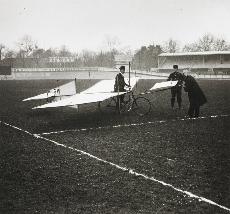 three men, one in uniform, with a bicycle-driven aircraft; 38 on tail; field has white lines; viewing stands in background
