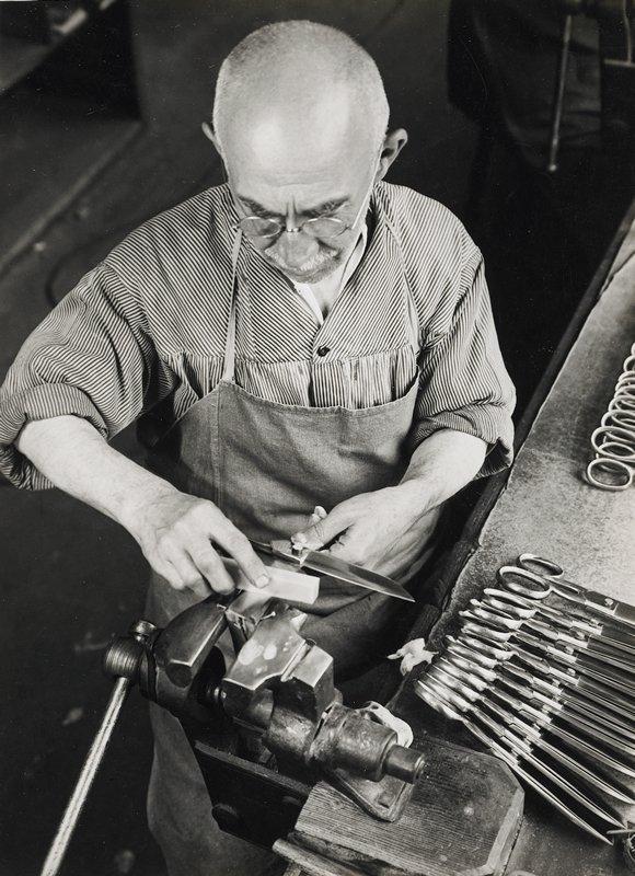 man sharpening scissors