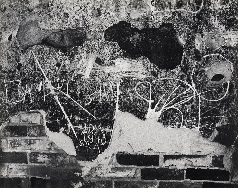 wall, partially exposed brick with writing, mostly not readable
