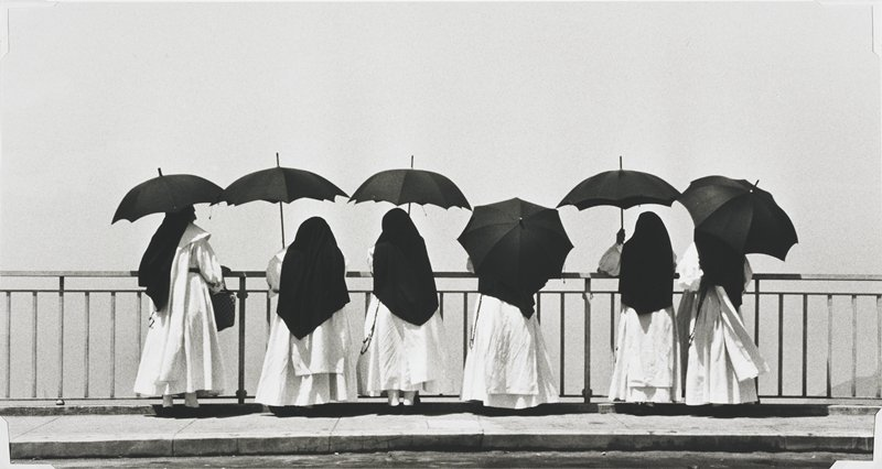six nuns along an iron railing holding black umbrellas; white habits, black veils; all facing away from camera