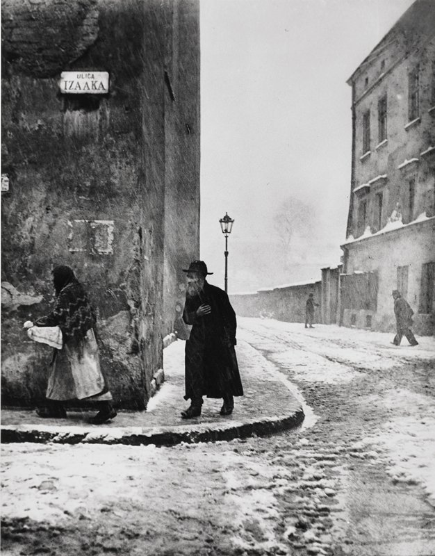 snow/slush covered street; woman carrying covered tray, bearded man wearing black hat and long coat behind; two other male pedestrians on right