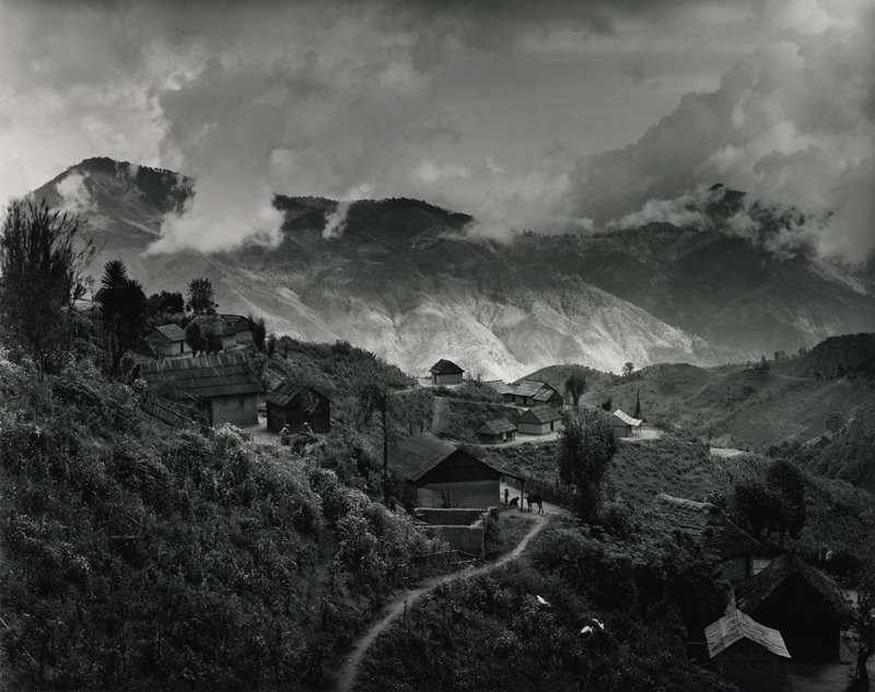 hillside village, path leading in from center front edge; buildings and people in foreground and middle ground, cloud-covered mountains in background