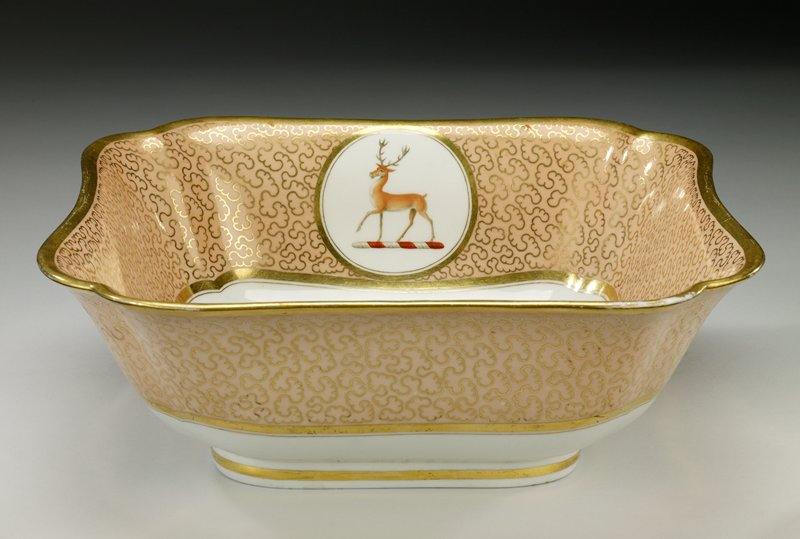 square dish with rounded, inward pointing corners; white with pink sides (interior and exterior) decorated with looping gold designs; two round cartouches with deer on red and white bases at opposite interior sides