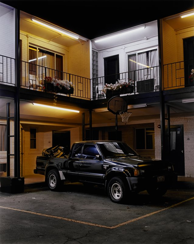 black pickup parked in front of an inner corner of a two-story motel; basketball hoop behind pickup; boxes of red and white flowers on second story railings