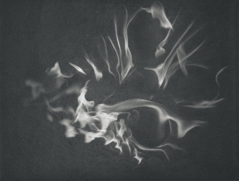 abstracted image; flames in a roughly teardrop shape, with three open areas, on a dark background