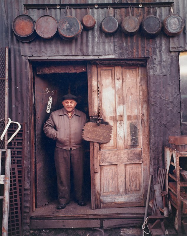 "man wearing a cap with his hands in his jacket pockets, standing in the doorway of a run-down corrugated metal building; eight cast iron pans hang above door; sign written in chalk on a board, hanging on door latch, reads: ""Working in the Back"""