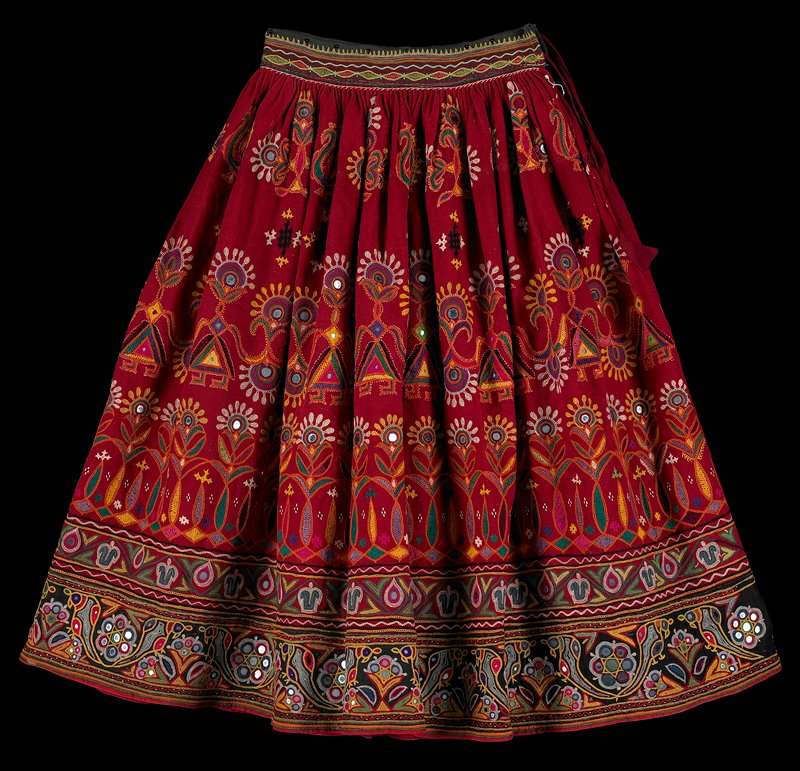 thick red fabric embroidered in multicolors with human forms alternating with flower forms and other bands of primarily floral motifs; birds and flowers in bottom band; peacocks in top band of body; mirrors; tie at waist