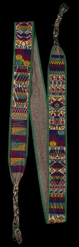 brown and tan on back; green edging; tan, brown, yellow, magenta, purple, green and orange designs of hands, animals and various geometric designs; braids at ends
