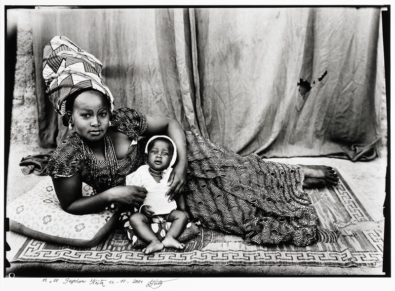 African woman reclining on a rug holding seated baby