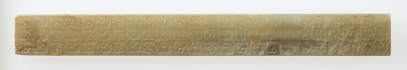 Tablet, rectangular, with relief. Pale green-gray translucent jade, partially calcified. Double-line engraved comma pattern design decorate the entire surface of the tablet (both sides).