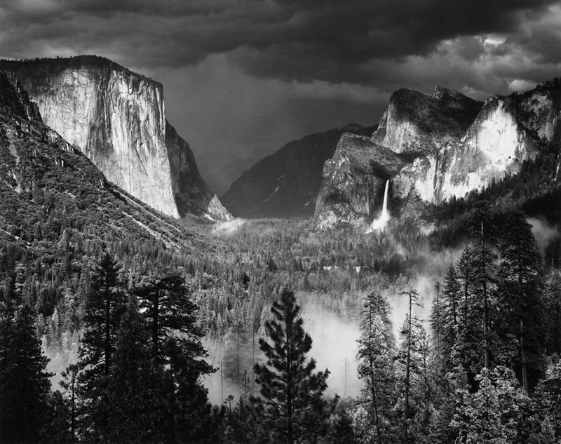 dark clouds above valley; cliffs on either side; waterfall on right; low clouds or fog in foreground behind pine trees