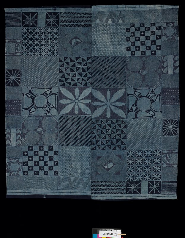 two panels, sewn together and hemmed on two sides; indigo with light blue patchwork- like designs with various geometric and zoomorphic designs; two floral motif blocks at center; starch resist