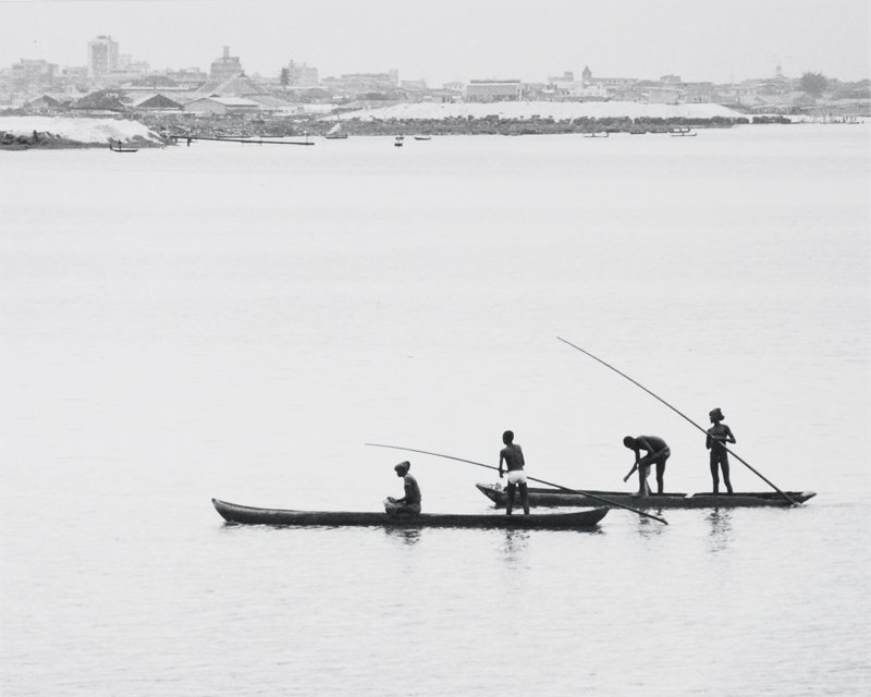 four persons in two boats on lagoon; two persons holding poles; city in distance