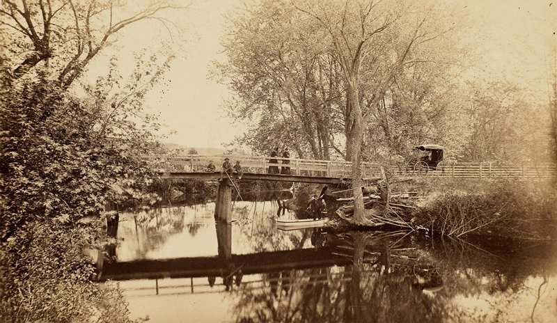 view of a bridge over calm water; man and two boys seated on bridge, fishing; two standing ladies look over railing; parked carriage at right; man and girl stand in boat near tree at shore; mounted on card with title and photographer's initials