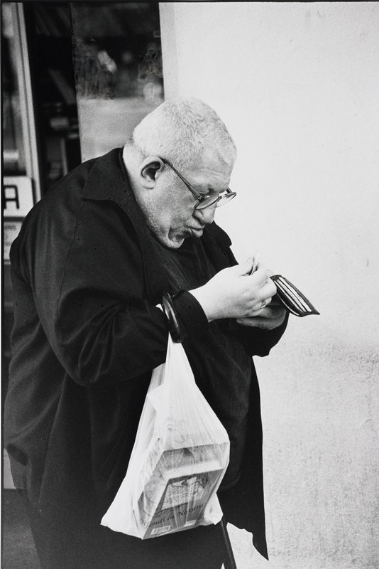 priest, grey hair and glasses, holding open wallet; plastic bag with books and a cane over proper right arm