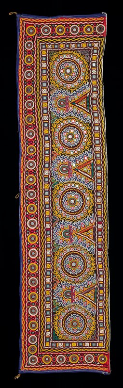 black fabric with red border on three sides; purple outer border on three sides; embroidered overall with geometric and round floral motifs; predominately white and yellow embroidery; embellished with mirrors