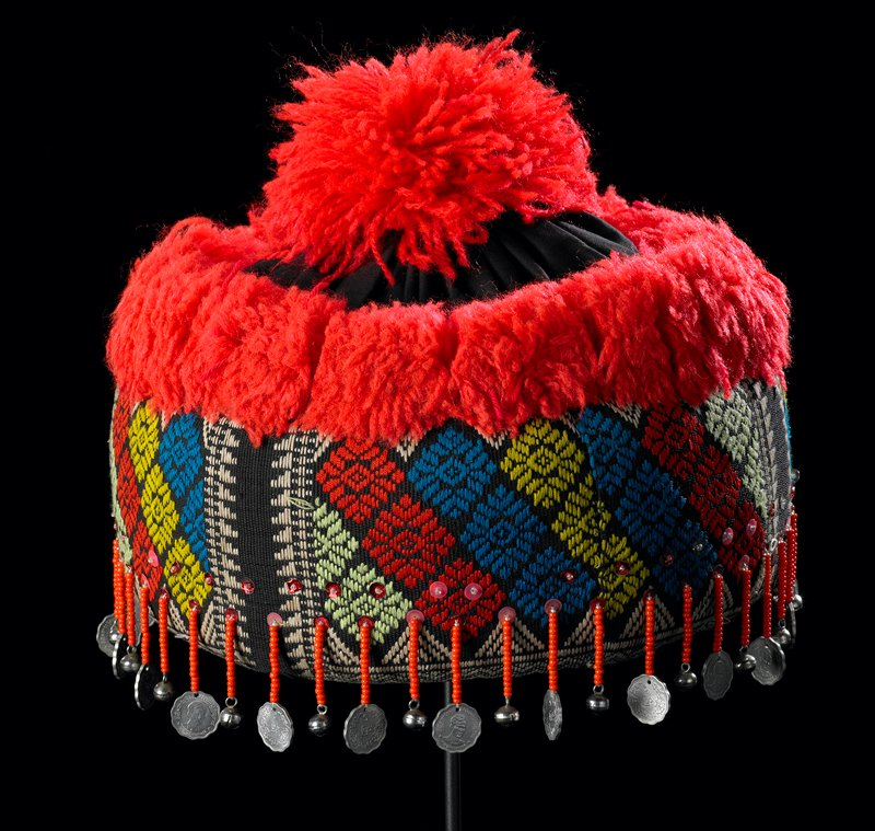 padded sides with black fabric woven with blue, tan, red, green and yellow diamond designs; red plush yarn around top edge and top pompon; sequins, and coins and bells suspended from orange beaded drops around back