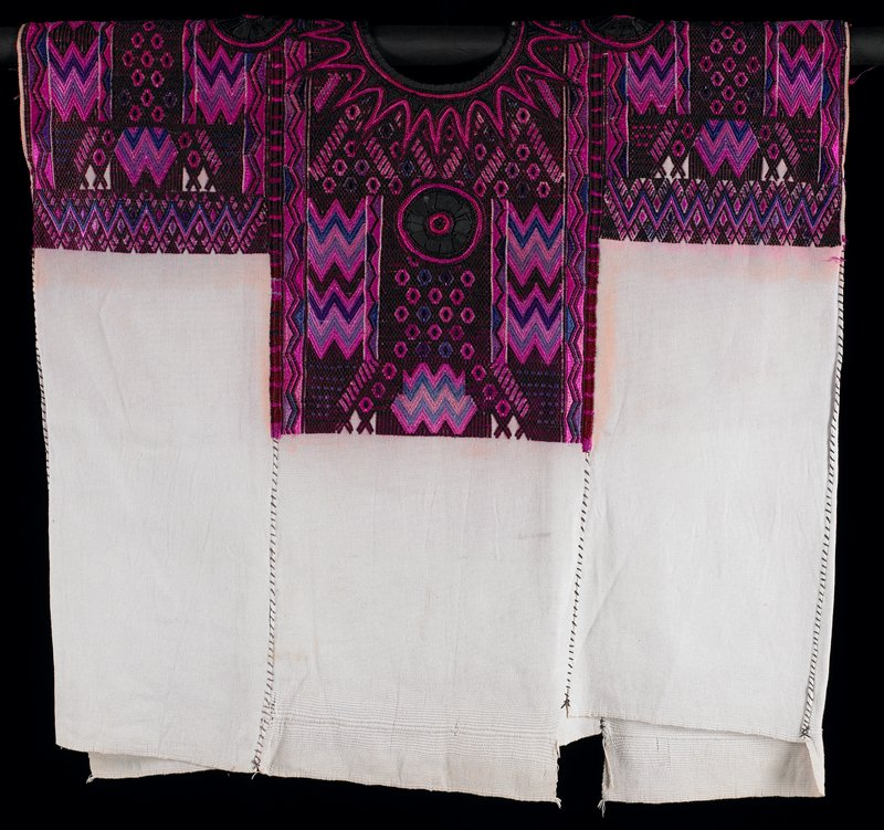 white (discolored to light pink); woven at top to create T-shape, front and back-various geometric motifs in dark maroon (predominate), dark purple, lilac, lavender, turquoise, medium pink, light pink and coral; black gathered appliqué rondels at chest, upper back and each shoulder; black collar with dark maroon and medium pink trim