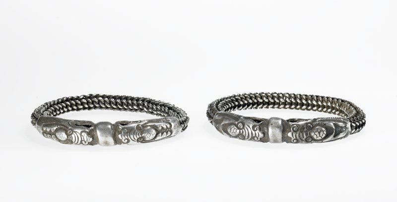 woven chain bracelet; dragon/snake (?) heads with open jaws; solid metal disc between open mouths; closed circle, no clasp