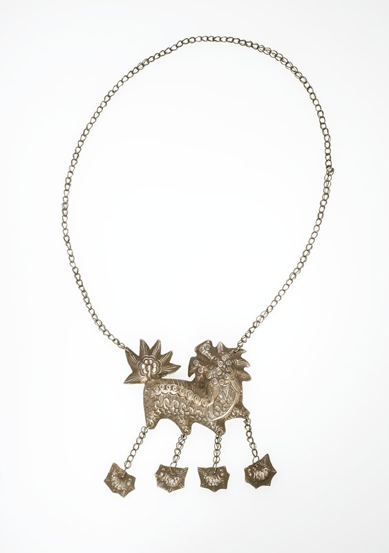 animal shape with four legs, each with a small pendant attached by chain; flower-like tail; pointed, cone shape motifs around head; many circular eye-like motifs on head and along back; 4 small pendants attached are irregularly shaped and 6 sided; motifs may be insects
