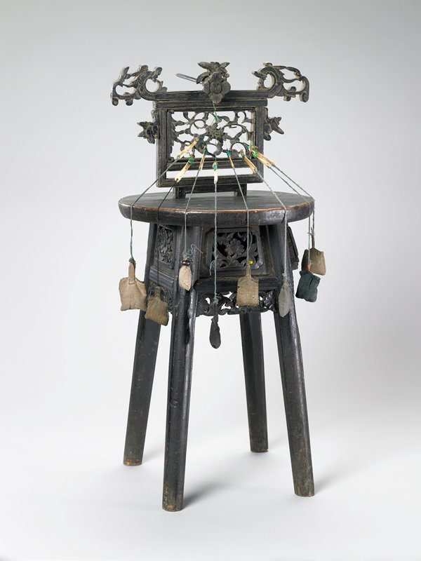 dark brown; four legs; rounded top/seat with openwork removable backrest or work holder (?); small drawer under seat; floral motifs carved on apron; spindle (?) with floral finial, attached with green and yellow braided cord and various threads to small cloth weights and ivory needles (or shuttles)