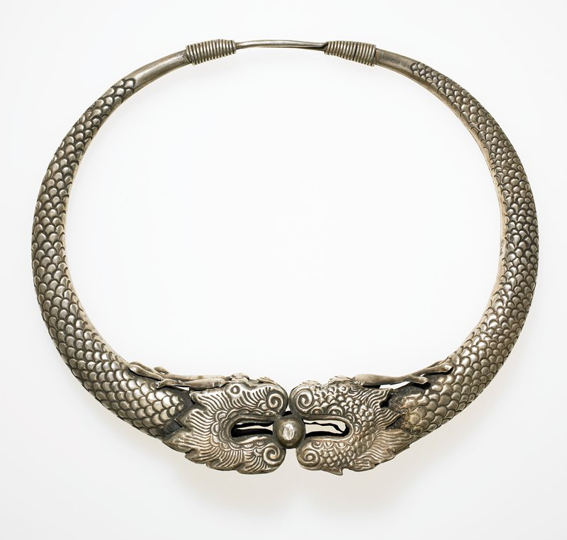 torque made from one ring of hollow silver; each half of the ring makes up a dragon; the dragon heads meet in the center where they are holding a sphere in their mouths; silver seems very thin on the dragon heads; sphere is actually a half sphere attached to the pins on either side; connecting portion in back is wrapped with thinner wire