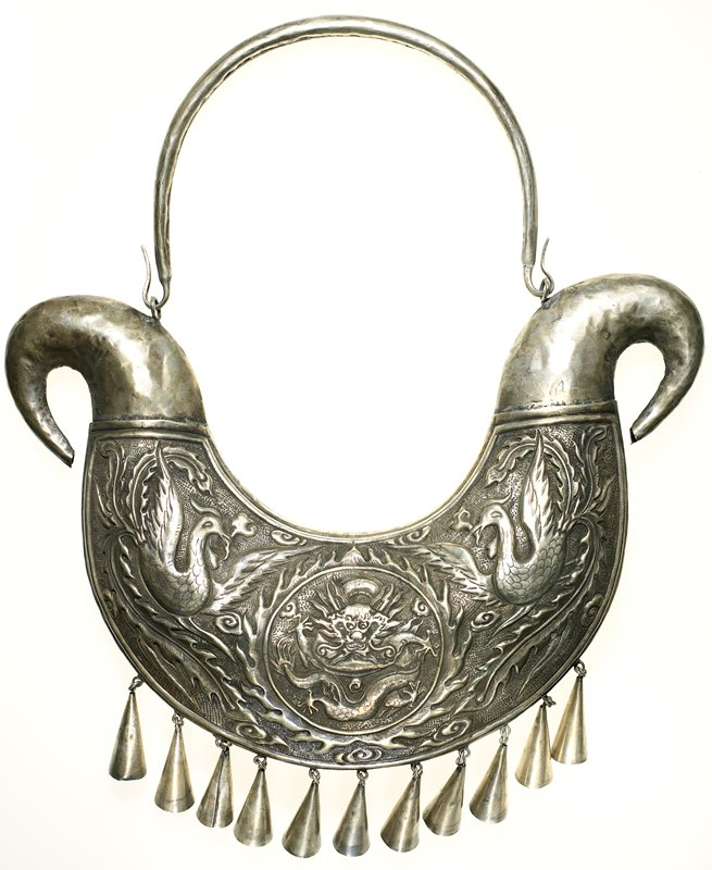 "rounded ring for back of neck; large ""puffed"" front pendant with scrolling ends; hammered designs of two birds flanking a flaming medallion with a dragon; birds have long tail feathers; eleven cone-shaped drops at bottom of pendant"