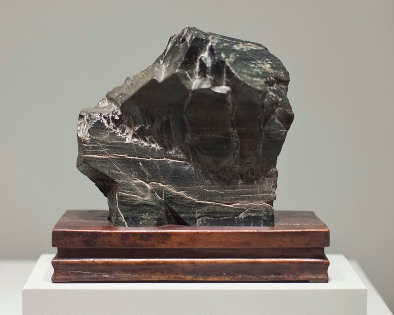 squat upright shape of horizontal, massed volumes with horizontal striations with an overhang to the front; stone dense and resonate with distinct underlying greenish tinge with lighter green veining and some buff striations