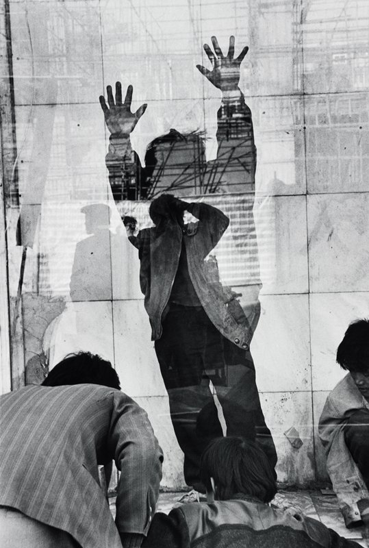 reflections or multiple images; figure standing with arms raised, wearing a jacket, in front of a marble tile wall, face shadowed; three men in foreground; tall scaffolding at top of image; shadowy heads and torsos at center
