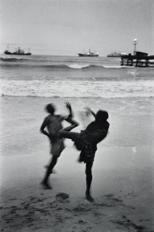 two blurry figures kicking each other on the beach; boats in background