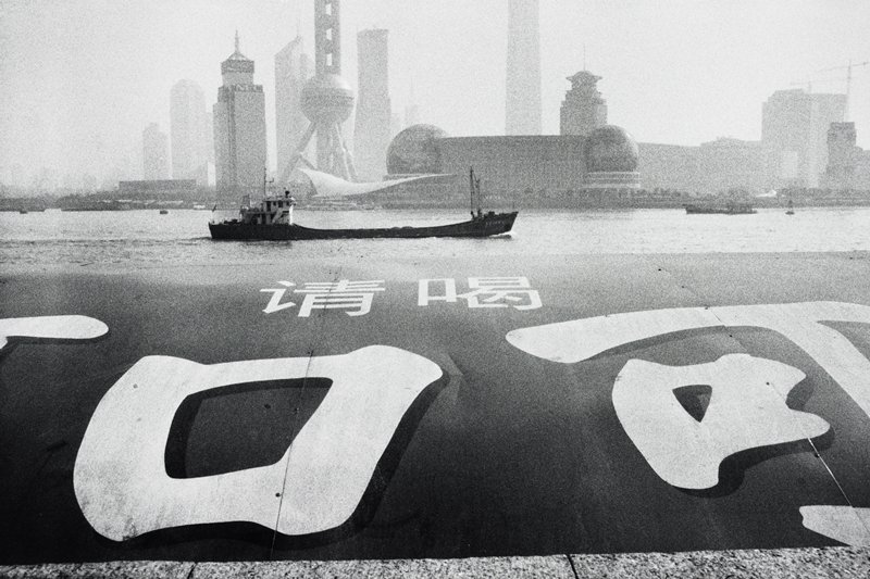 very large text characters in foreground; ship on water in middle ground; city in background