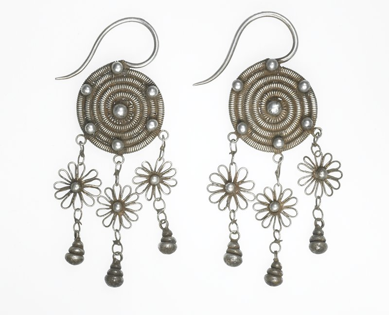 pair of earrings; each main body is a circle of tightly-coiled wire wrapped around itself into a circle; five spheres run around the edge, one sphere is in the very center; three chains with wire flowers and spheres on the bottom dangle down; decorations are on both sides; ear piece is sharp wire piece curved