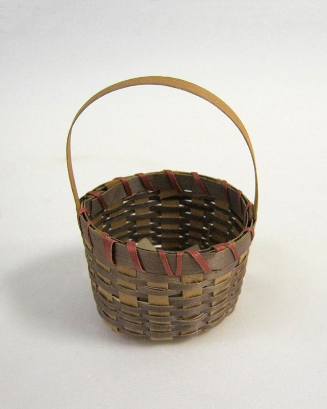 small round handled basket with flat bottom; brown and tan body with red loops around top; tan handle