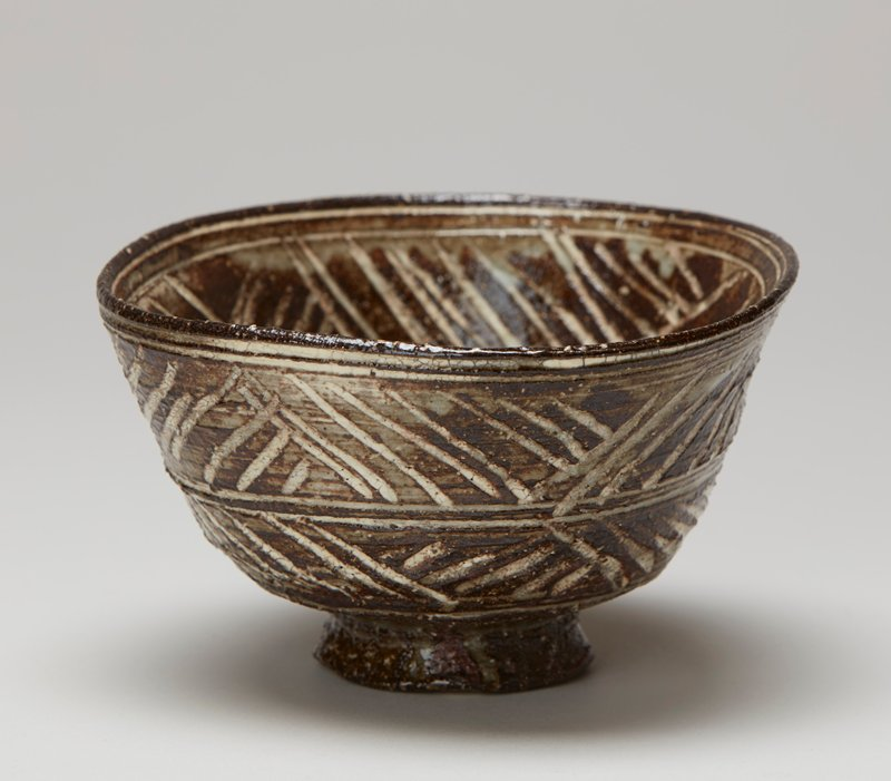 tea bowl; rather tall foot ring, slightly tapering inward at top; rounded bowl shape, slightly pushed in on one side; incised white designs on brown--two bands of diagonal lines on exterior--circles at bottom interior and diagonal lines at interior sides