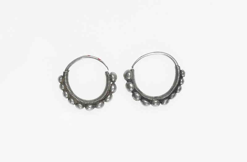pair of small earrings; each has one loop of thin silver with a pointed end; main body of loop is covered in wrapped wire; wire has ten small spheres hanging down