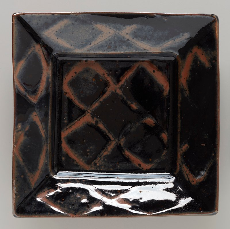 square raised foot; square base with articulated rim; light brown on dark brown--diamond pattern on top surface and mottled areas on underside