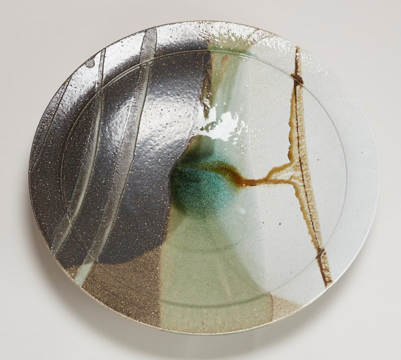 very large; slightly concave base; saucer shaped; grey on bottom; top has bands and triangular areas of color with round area in center of thick green glaze--off-white, greys, browns, greens