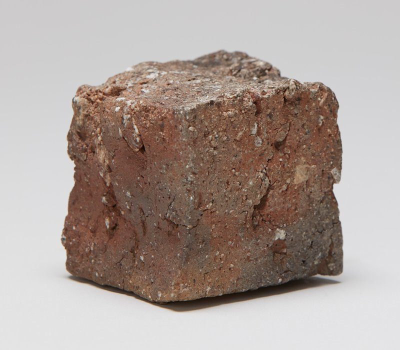 rough cube of clay; shades of brown and tan